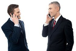 Two businessmen talking on the phone and looking at each other.