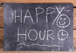 Happy hour text on a blackboard.