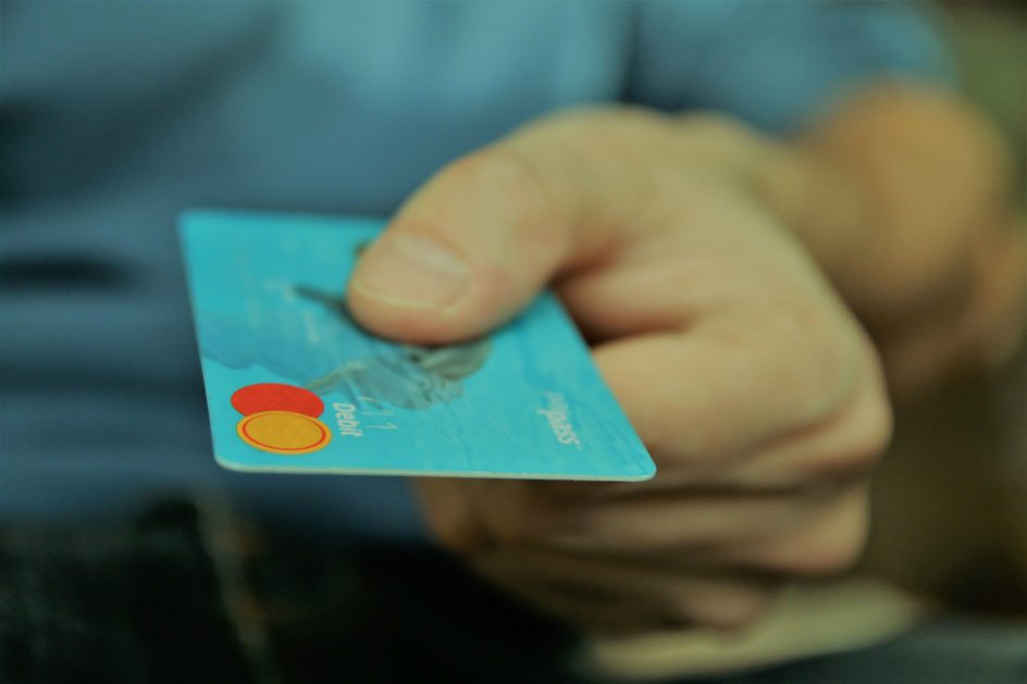 A person holding out a debit card.