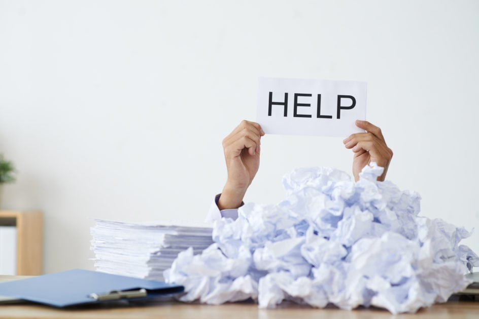 Person under heap of crumpled papers with hand holding a help sign.