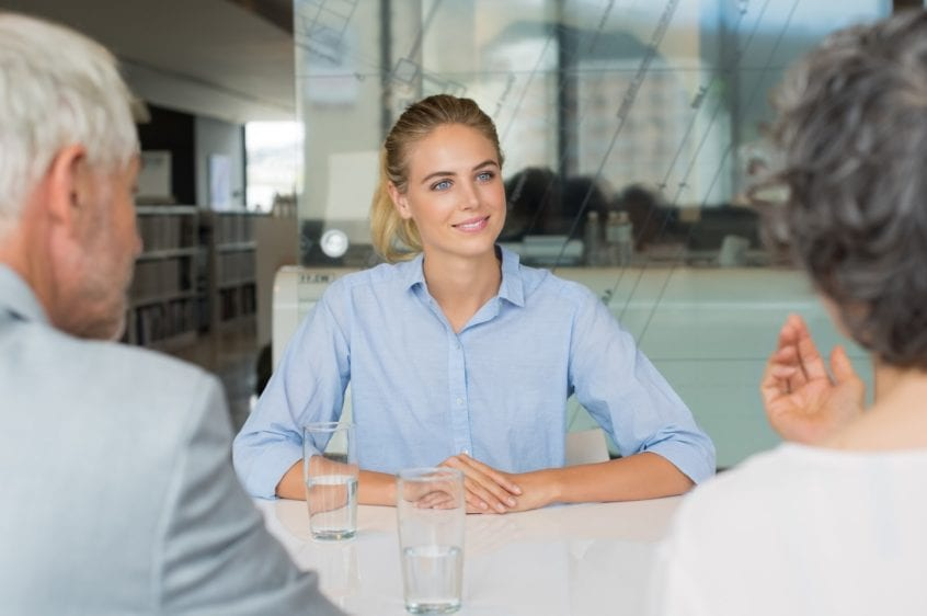 Portrait of beautiful young woman sitting in front of manager and senior leader during a job interview. Senior business people in conversation with a young business woman. Recruiter checking the candidate during job interview.