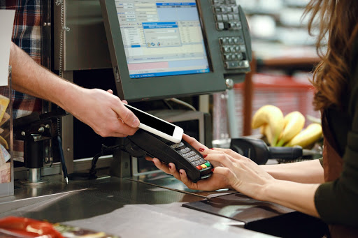 A cashier scanning a smartphone for purchase.